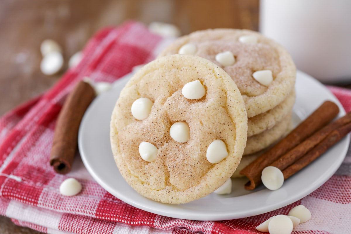 Snickerdoodle white chocolate chip cookies stacked on a white plate