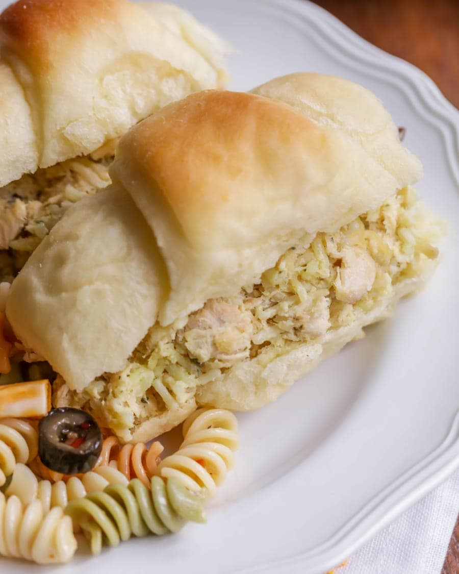 Close up of chicken salad served in a roll on a white plate