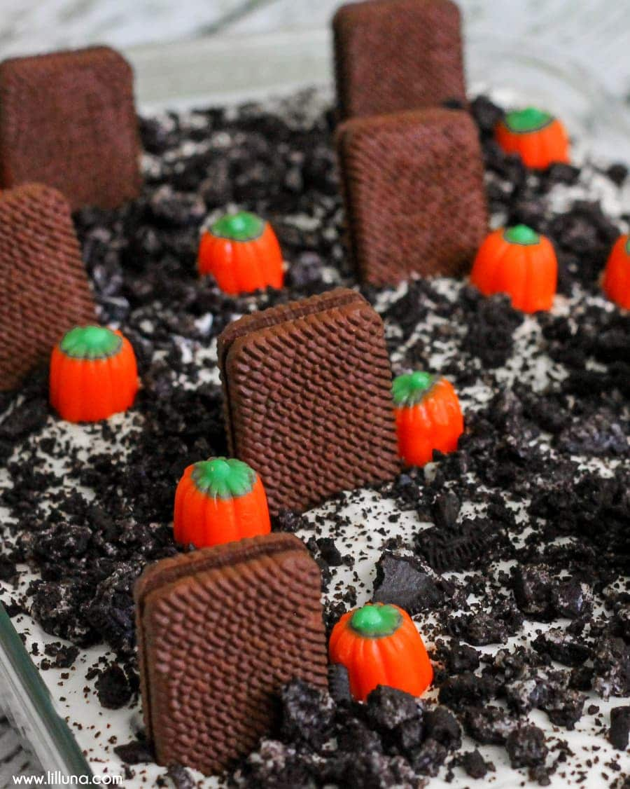 Graveyard Dirt Cake! Perfect dessert for Halloween! { lilluna.com } Crushed oreos, pudding, cream cheese, cool whip, candy pumpkins, & chocolate cookies make this a hit!