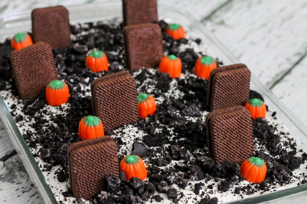 Graveyard dirt cake topped with mallow pumpkins in a glass baking dish