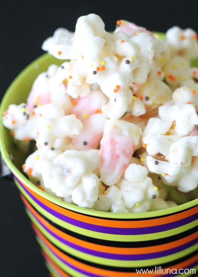 Candy Corn Popcorn Mix!! A delicious treat that all will love!! So easy to make! Popcorn and candy corn coated with melted white chocolate and sprinkles!