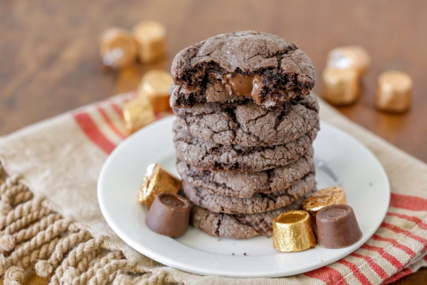 Gooey rolo cookies stacked on a plate surrounded by rolo candies
