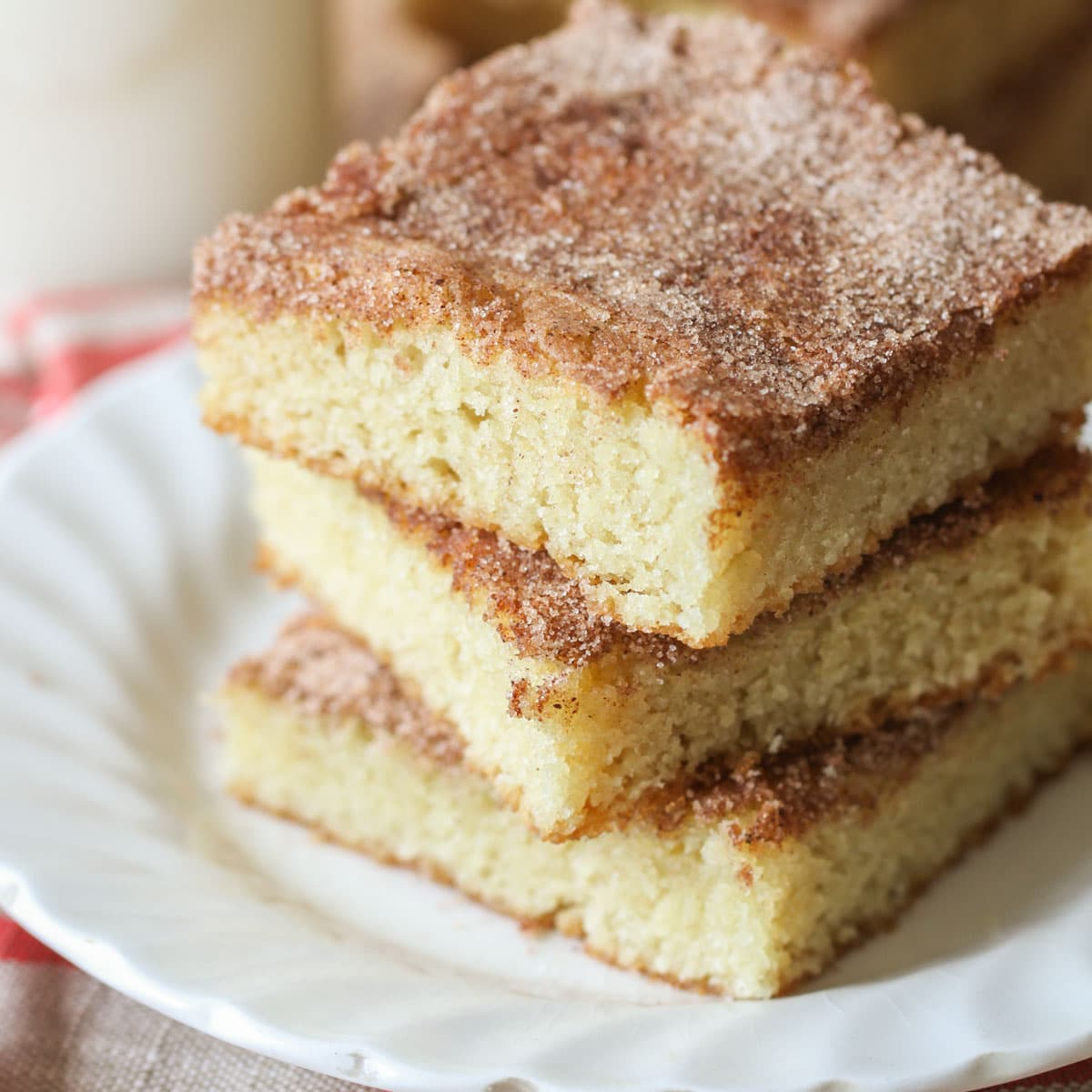 Three snickerdoodle blondies stacked on a white plate