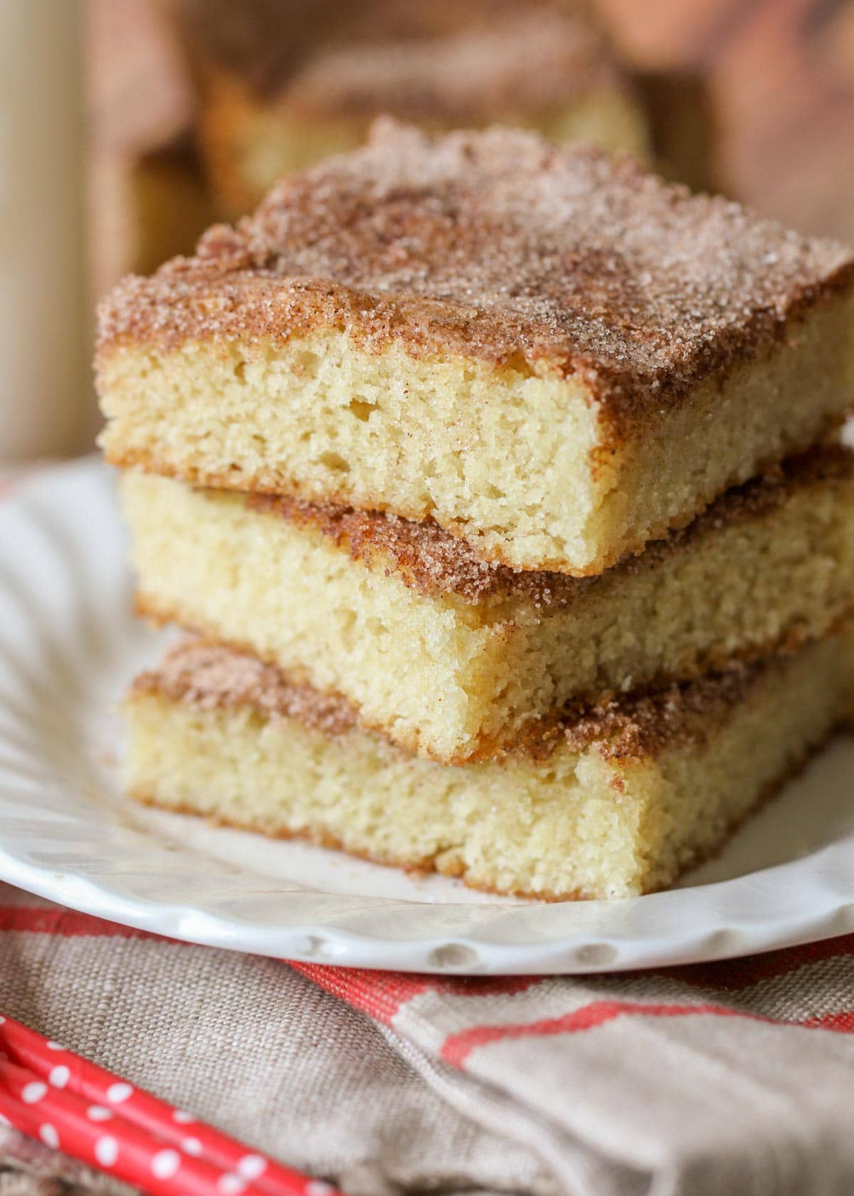 Snickerdoodle blondies stacked on a white plate