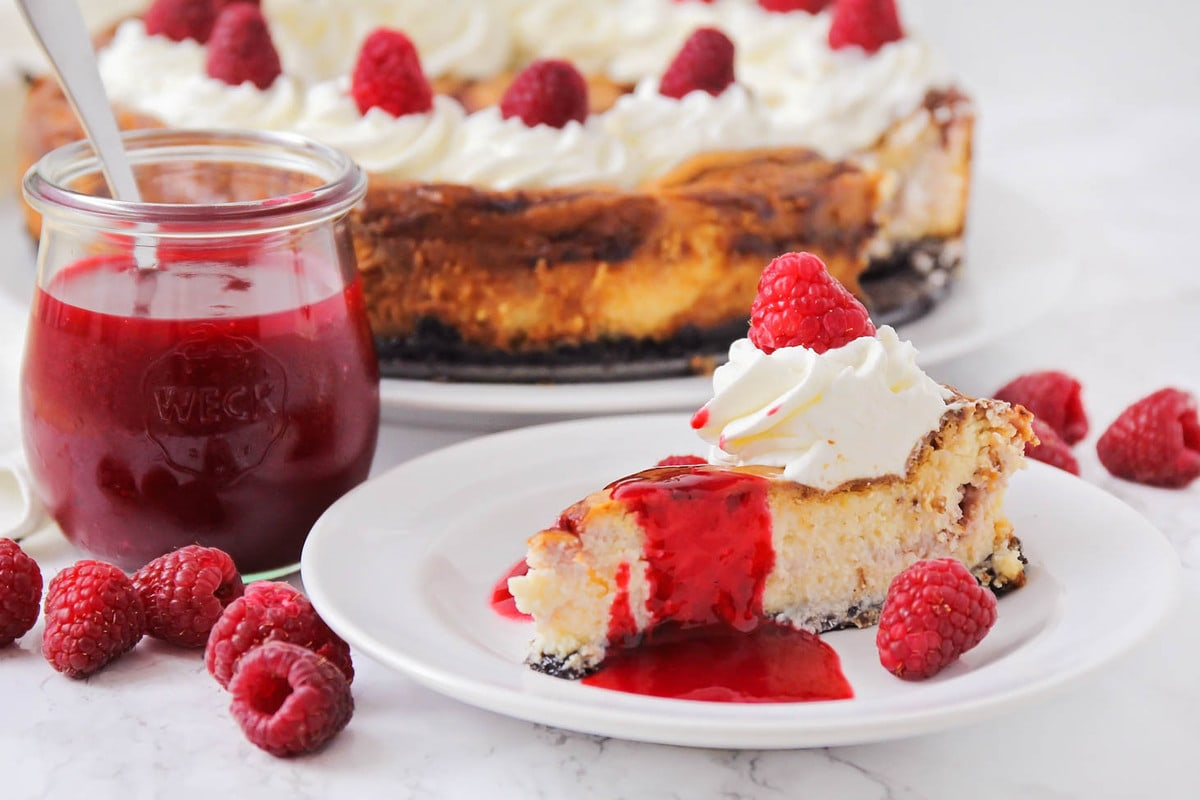 White chocolate raspberry cheesecake on a white plate topped with raspberry sauce