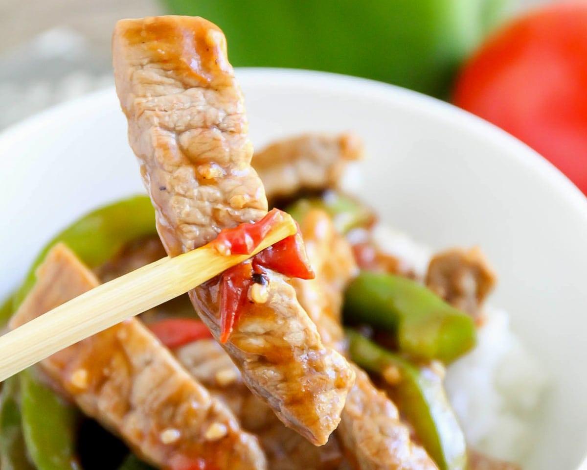 Pepper Steak held in chopsticks over a bowl
