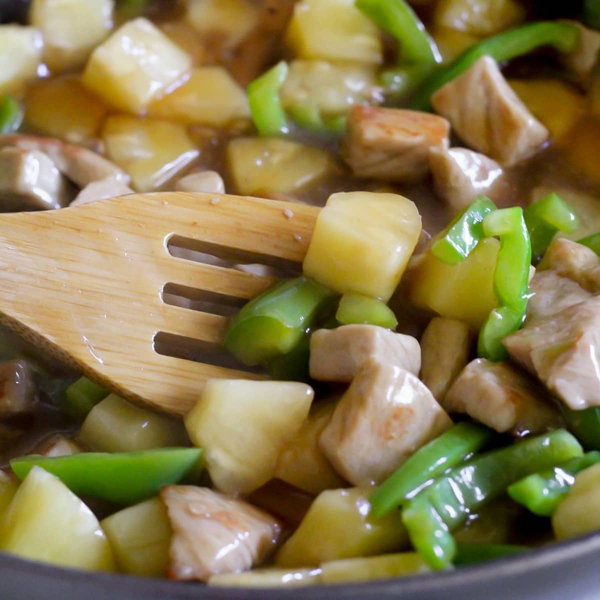Sweet and Sour Pork with green peppers and pineapple being stir fried in pan