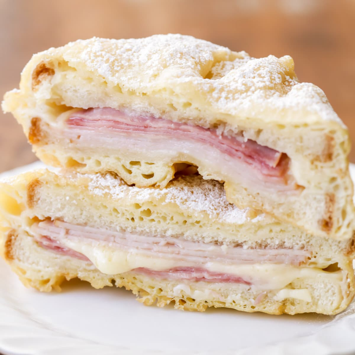 monte cristo sandwich cut in half and stacked on a white plate