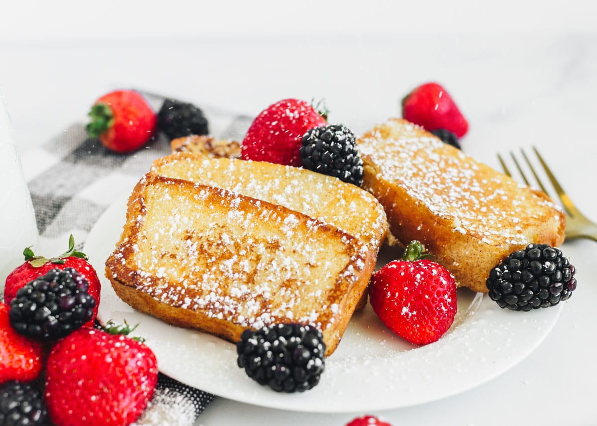 Pound cake french toast topped with powdered sugar and fresh berries