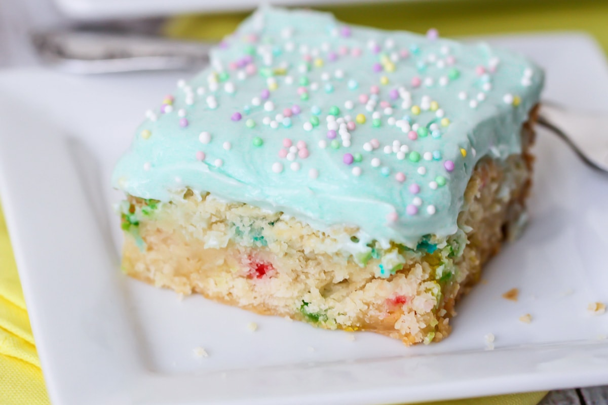 Slice of funfetti blondies covered in blue frosting and sprinkles