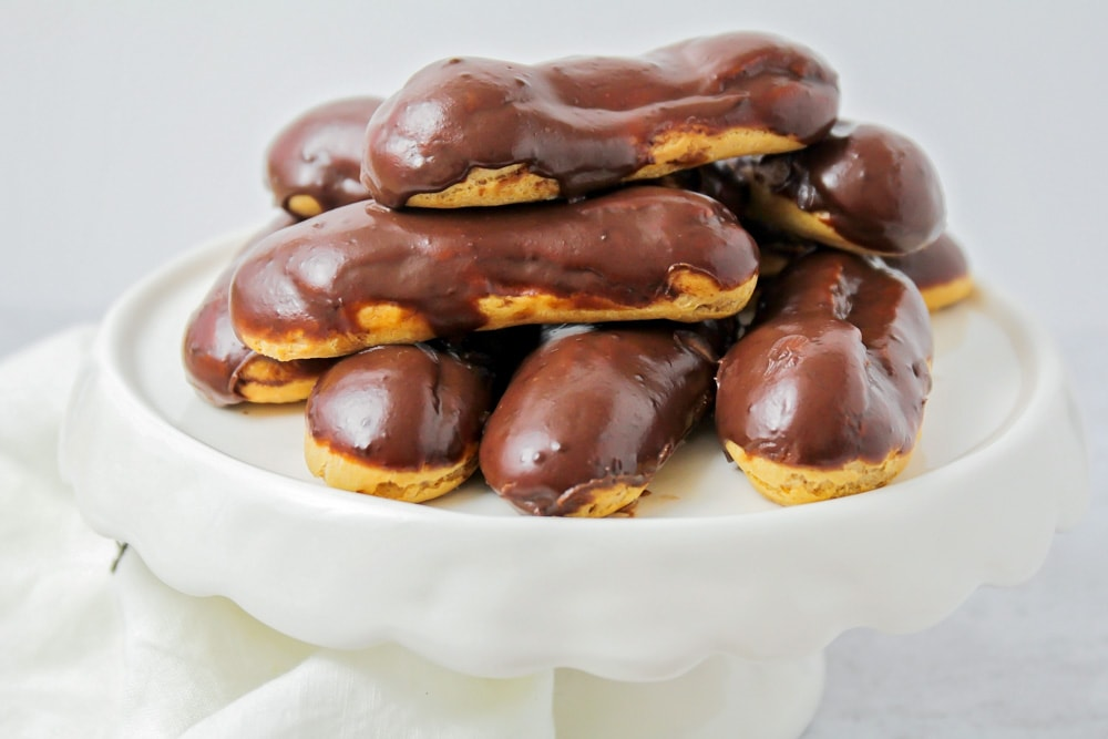 Homemade eclairs on a white serving platter