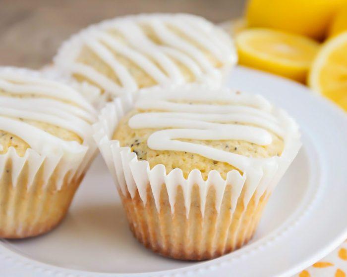 Glazed lemon poppyseed muffins on a white plate