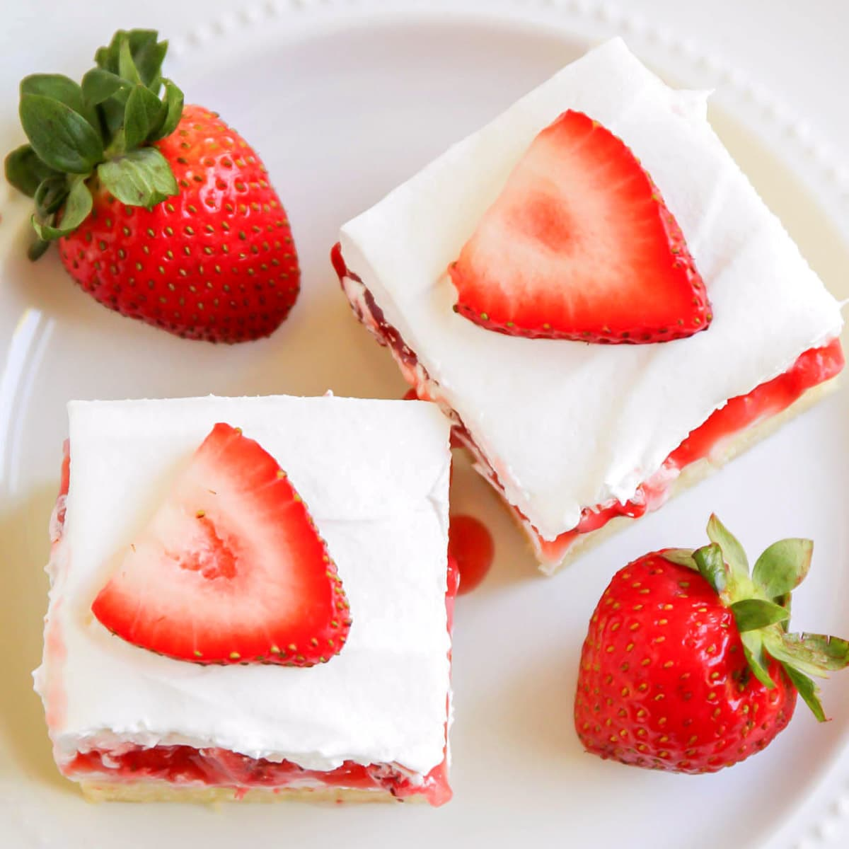 Strawberry cream cheese bars on a white plate