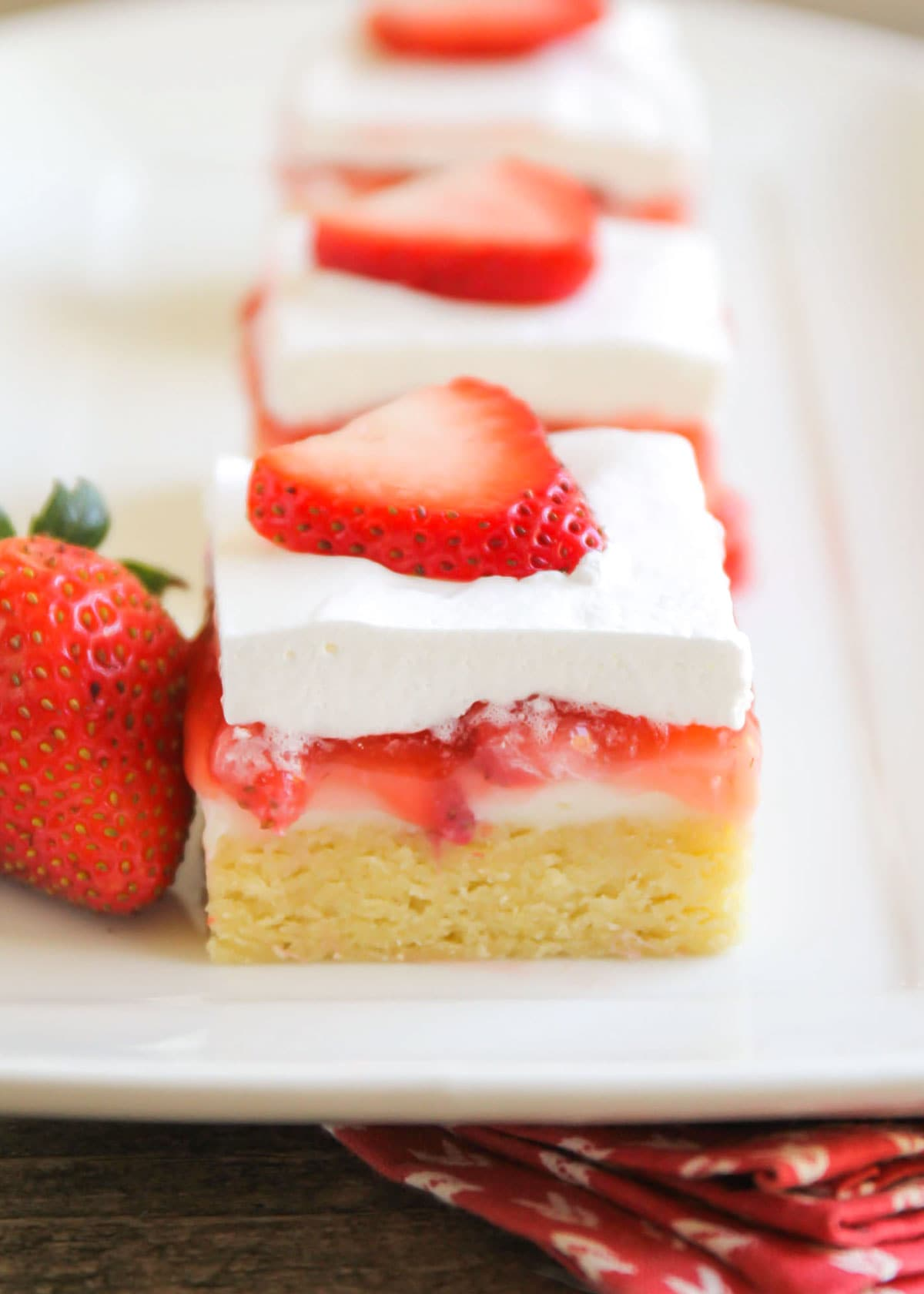 Strawberry cream cheese dessert bars on a white serving platter