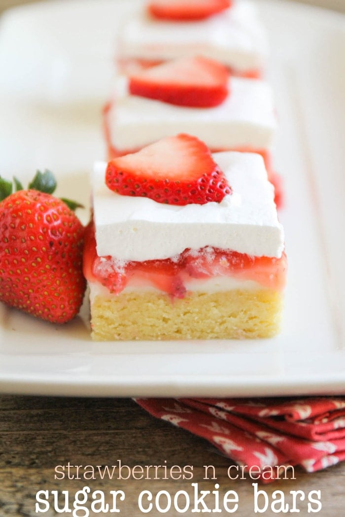 Strawberries N Cream Sugar Cookie Bars - so delicious!! Our family loves this recipe! A yummy sugar cookie bottom with a cream cheese, strawberry, and white chocolate chip middle and topped with cool whip!