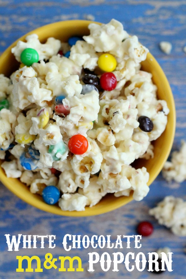Our favorite movie snack - White Chocolate M&M Popcorn! Melted vanilla bark poured over popcorn with m&m's mixed in!!