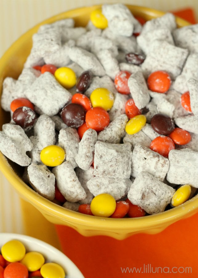 Reeses Pieces Puppy Chow recipe on { lilluna.com } Chex cereal, chocolate chips, & peanut butter, mixed in powdered sugar & tossed with reeses pieces!!