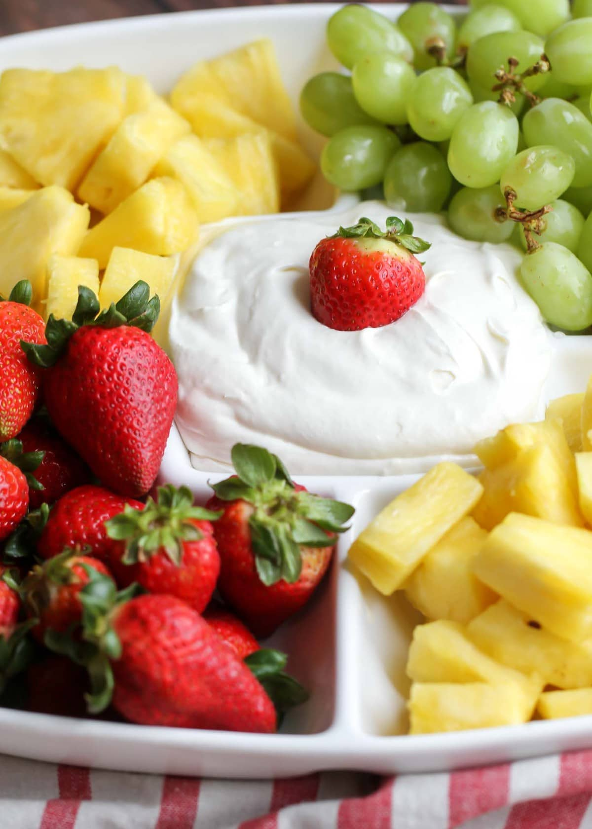 Cream Cheese Fruit Dip in white platter with strawberries, pineapple and green grapes around it