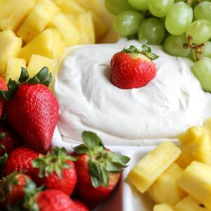 cream cheese marshmallow fruit dip on platter with strawberry on top with other fruits around it