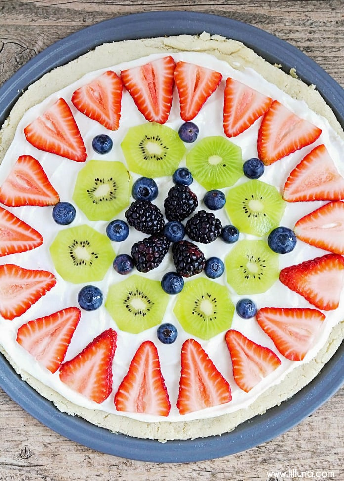 The BEST Fruit Pizza recipe ever! A super soft cookie dough with a pineapple cream cheese frosting topped with your favorite fruit!
