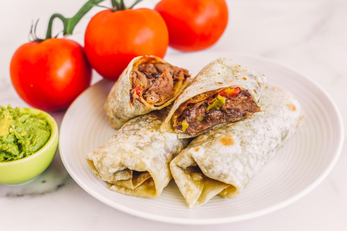 Green chili burritos on a plate with one cut in half