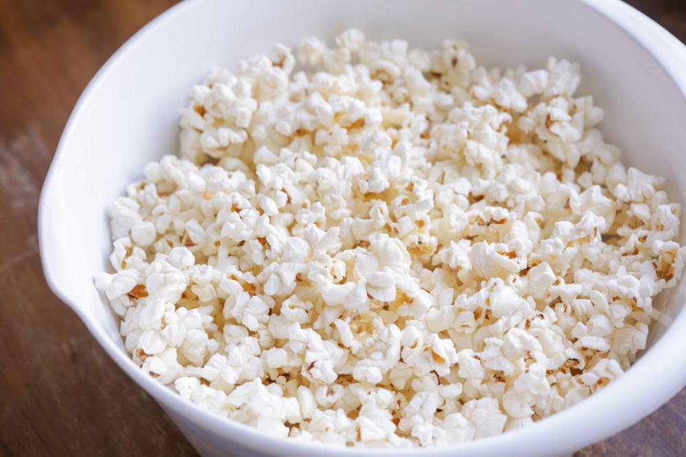 popcorn in a white bowl to use for pumpkin snack mix recipe