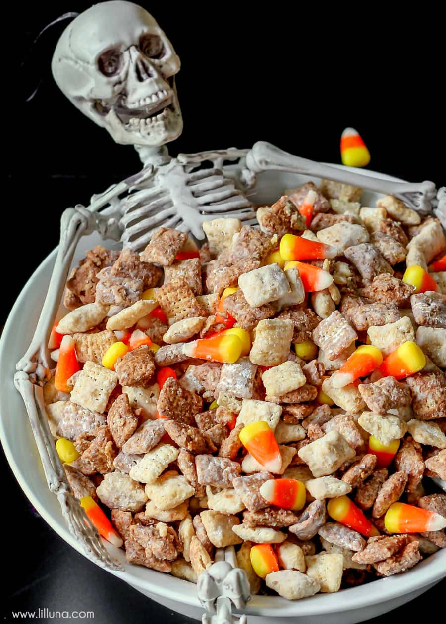 Black and White Halloween Puppy Chow recipe on { lilluna.com } Recipe includes white chocolate chips, milk chocolate chips, powdered sugar, chex cereal, & candy corns.