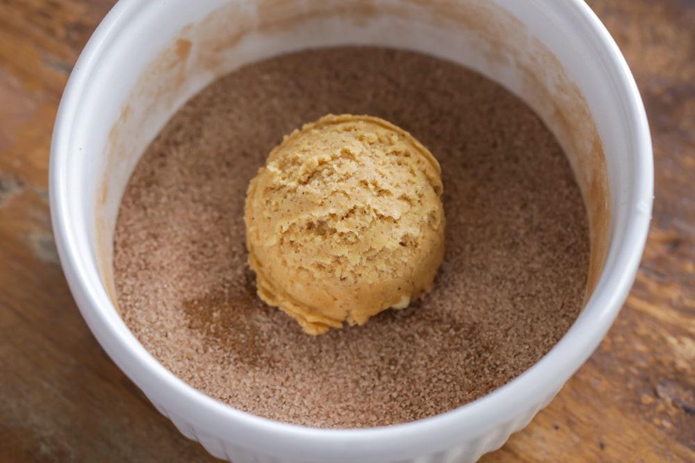 Pumpkin snickerdoodle cookie dough being coated in cinnamon sugar