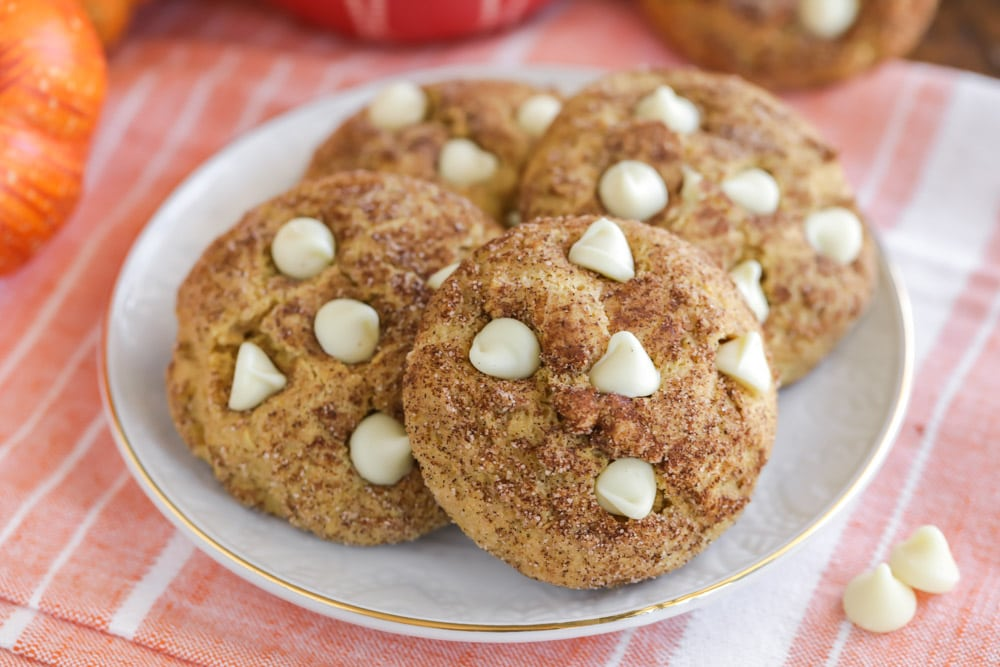 Pumpkin Snickerdoodles topped with white chocolate chips on a white plate