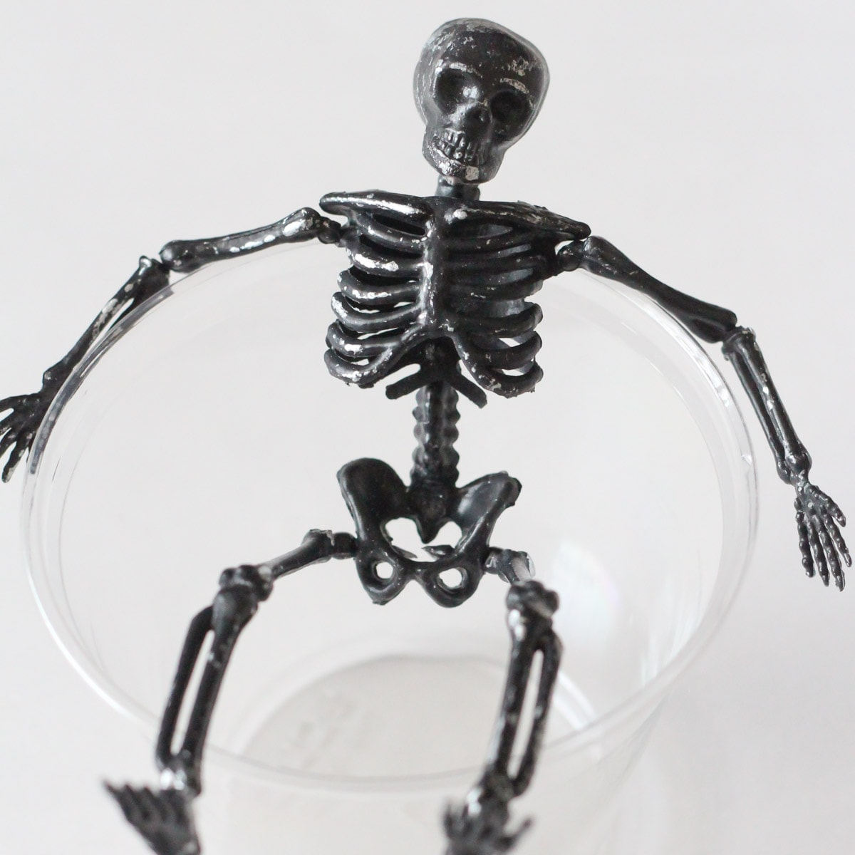 Small black skeleton and clear plastic cup