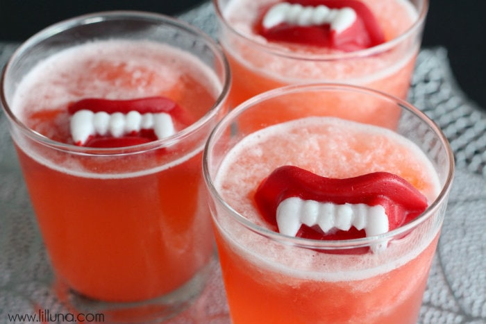 Halloween Slushy Punch Recipe with Wax Lips on { lilluna.com } Ingredients include strawberry jello, pineapple juice, orange juice, & lemon lime soda!