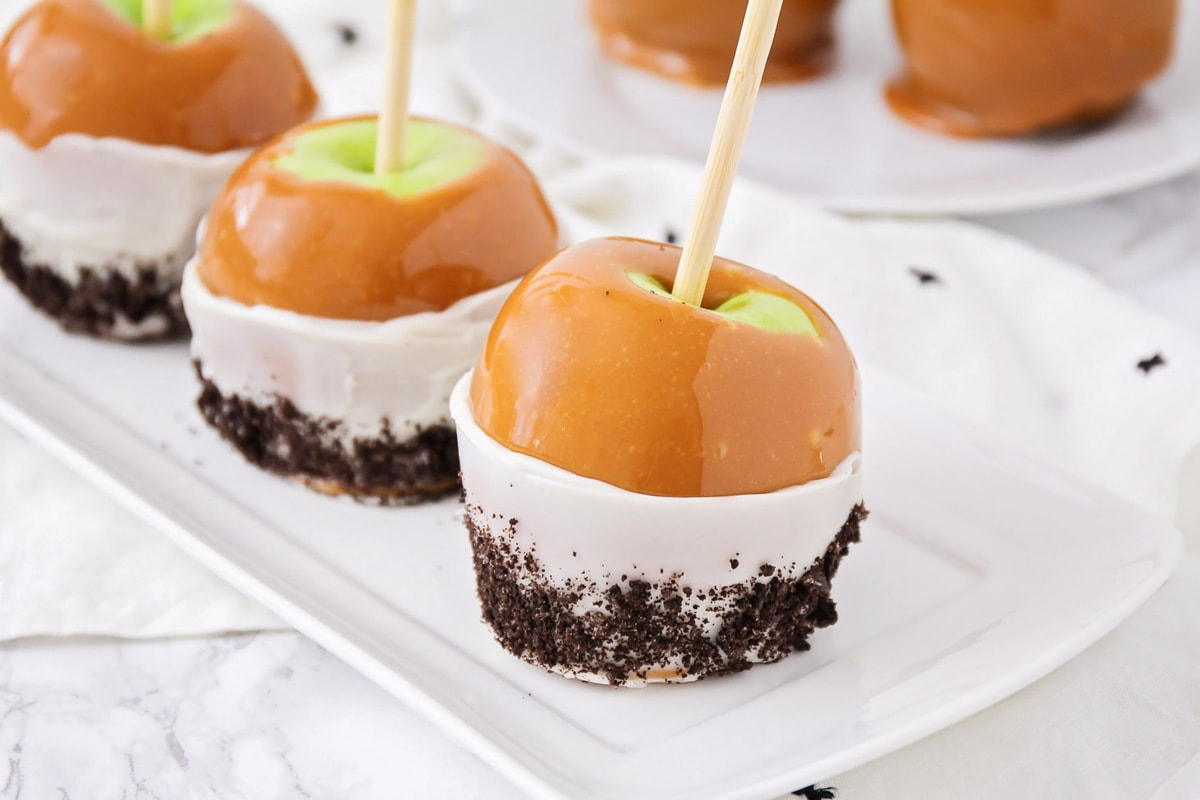Homemade caramel apples on white serving tray