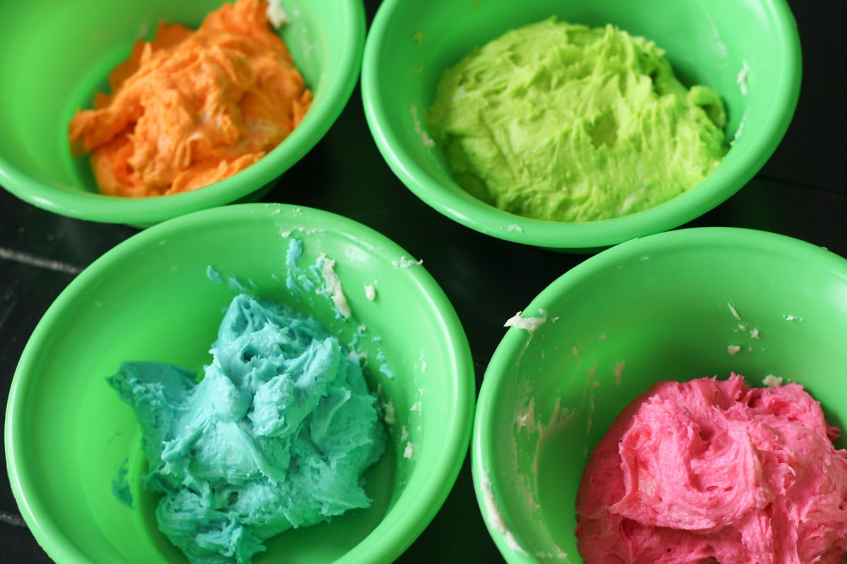Orange, green, blue, and pink cookie dough in separate bowls.