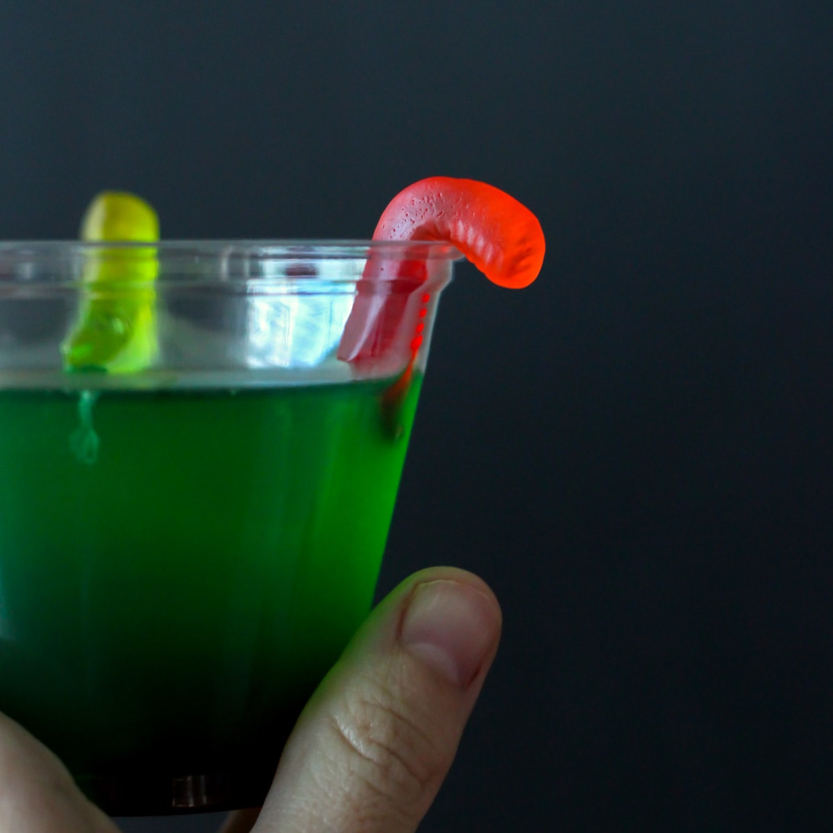 Green Jello in a clear cup with gummy worms