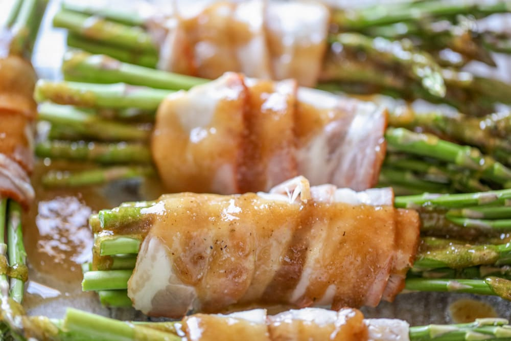 Asparagus wrapped bacon in sauce