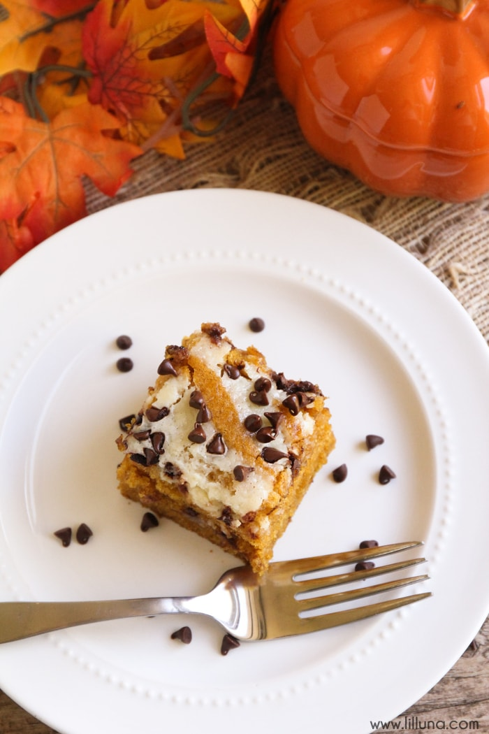 Pumpkin Cream Cheese Bars - a delicious fall recipe of pumpkin cake swirled with cream cheese and topped with mini chocolate chips! SO GOOD!!