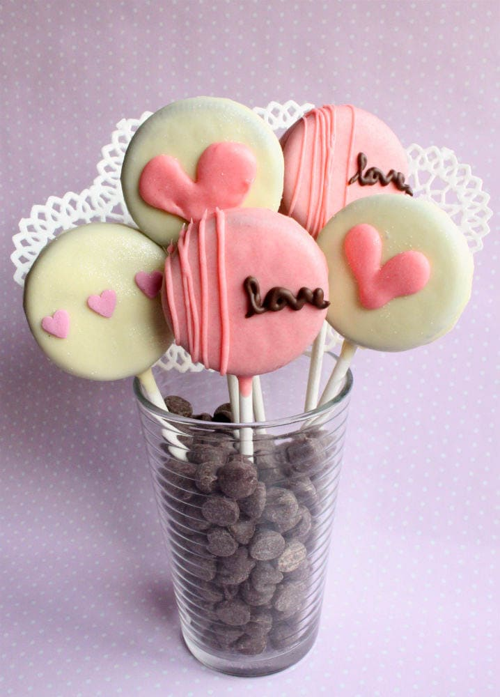 CUTE Valentine's Oreo Pops - recipe on { lilluna.com } So cute and delicious! Ingredients include oreos, dark chocolate chips, white chocolate bars, sprinkles, & pink food coloring!