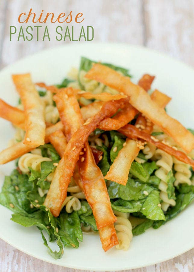 Chinese Pasta Salad recipe. So simple and so delicious! { lilluna.com } Simple ingredients include, romaine, pasta, wonton strips, shredded chicken, sesame seeds, & sliced almonds in a yummy Asian dressing.
