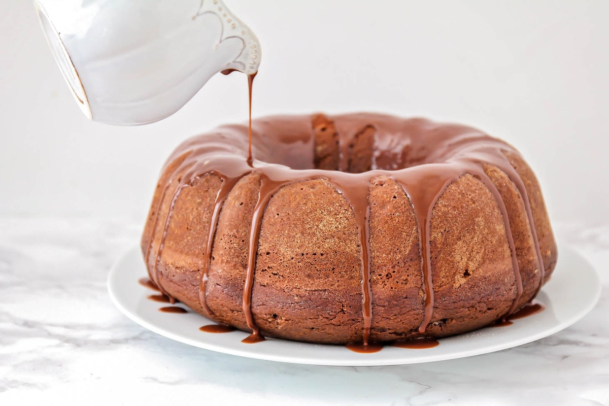 Easy chocolate bundt cake with chocolate ganache being poured on