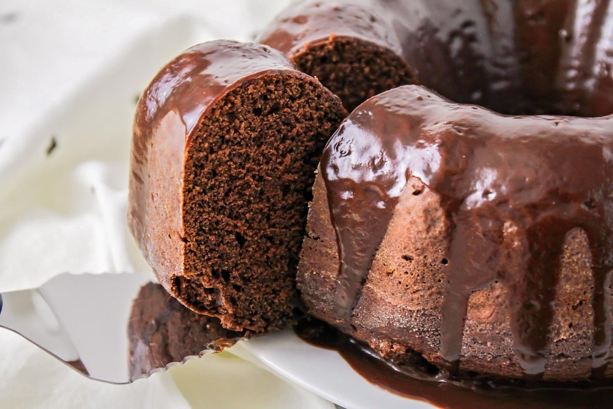 Chocolate bunt cake with a slice on a cake server