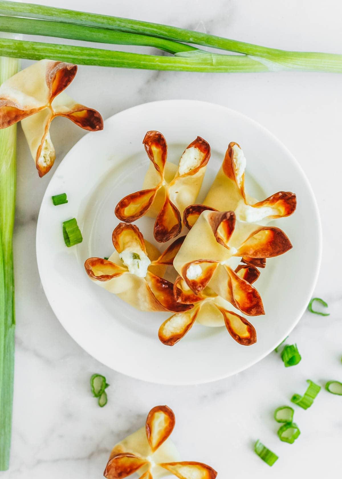 Baked cream cheese rangoons piled onto a plate
