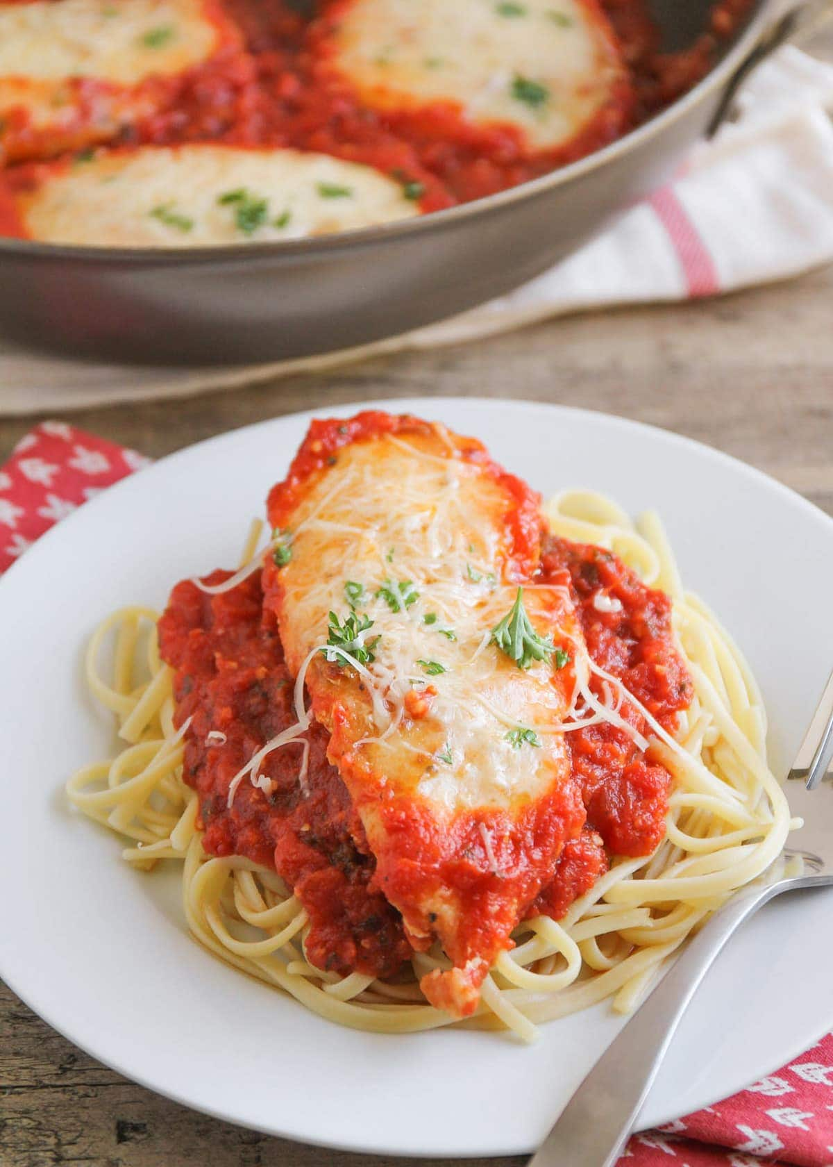 Chicken Parmigiana on pasta on white plate