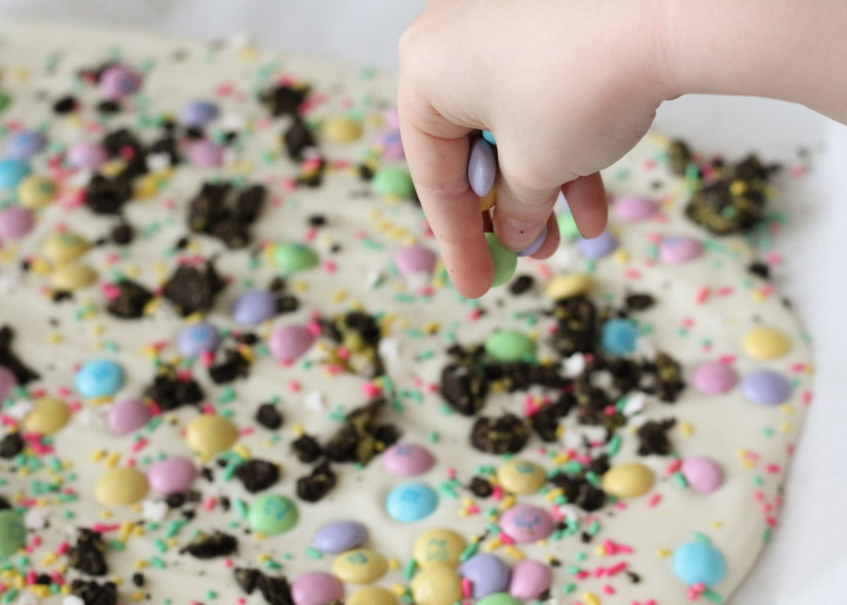 A hand sprinkling candy on top of oreo bark