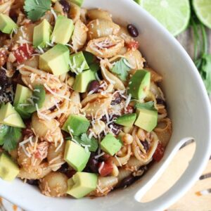 taco pasta salad with avocado and beans in white bowl