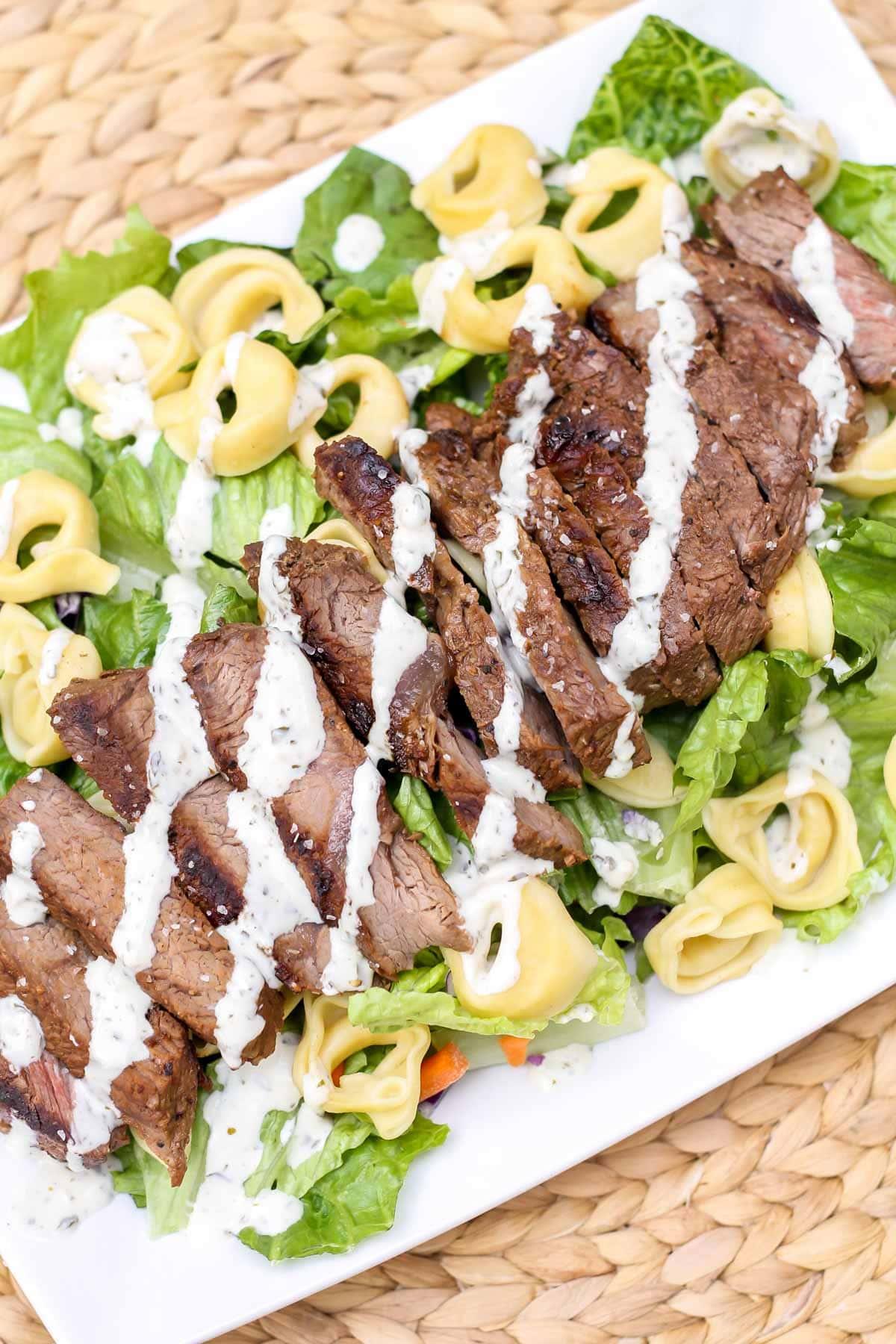 Steak and tortellini salad dressed on a white plate