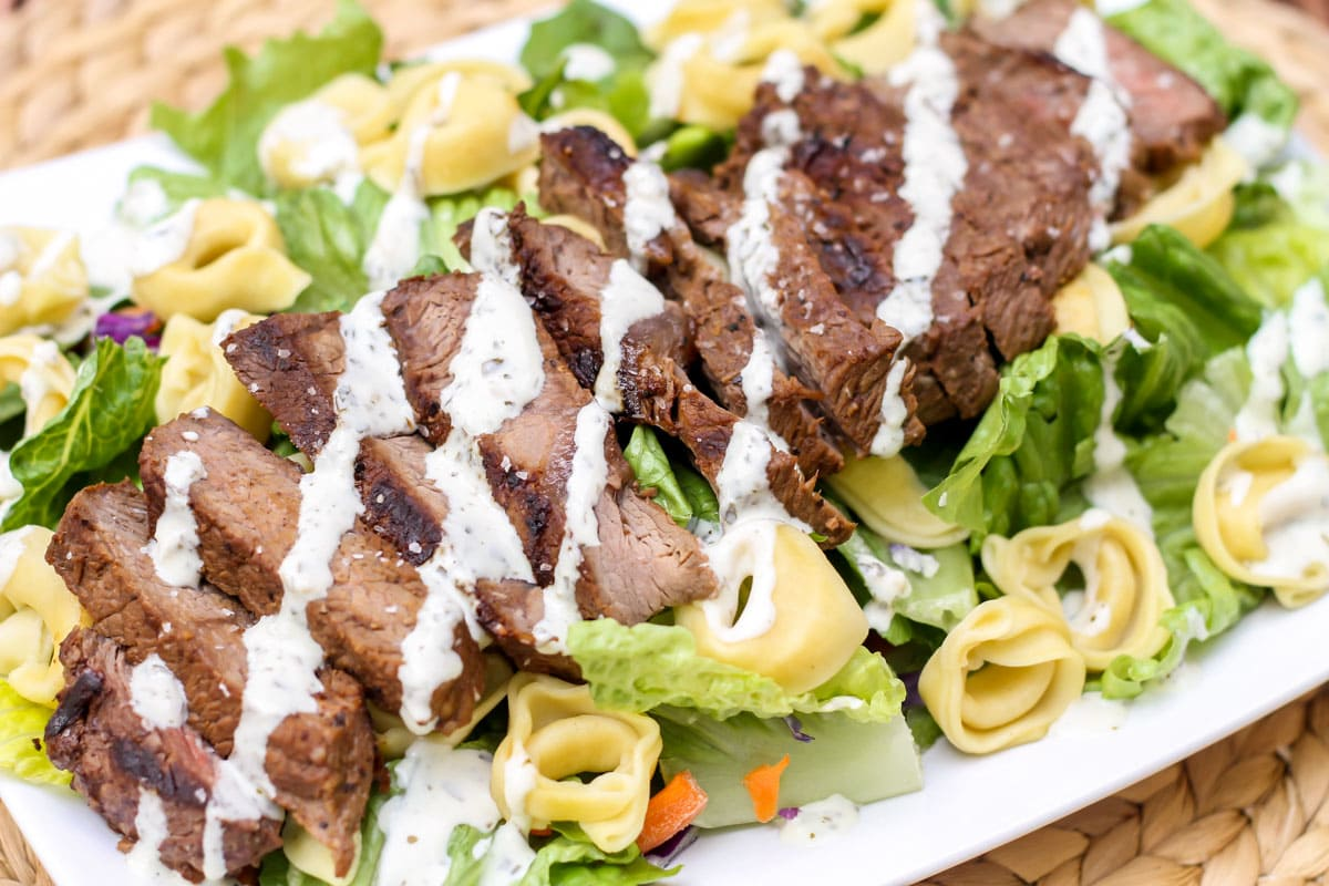 Steak and tortellini salad on a white plate.