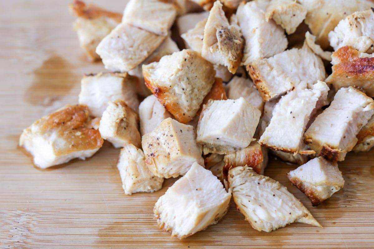cubed cooked chicken on a cutting board