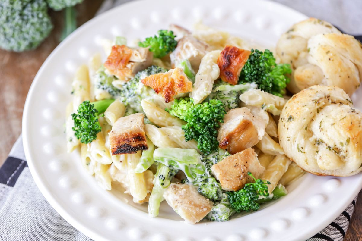 chicken broccoli alfredo served with garlic knots on a white plate