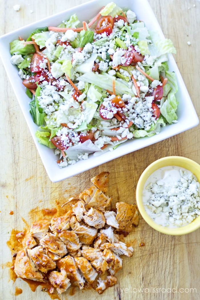Spicy Buffalo Chicken Salad - YUMMY!! Recipe on { lilluna.com } Ingredients include chicken tenders, buffalo wing sauce, lettuce, crumbled blue cheese, ranch, and your favorite salad mix-ins.