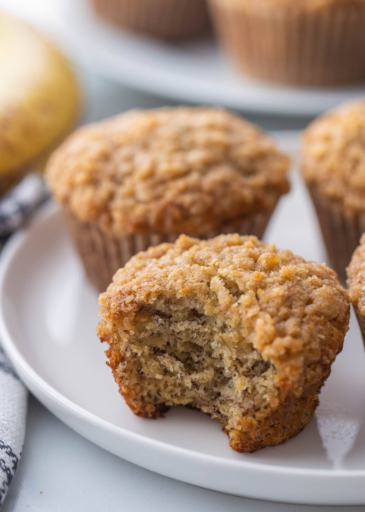 banana crumb muffins on a white plate with bite missing